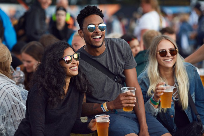 Friends having a beer together at an outdoor event.
