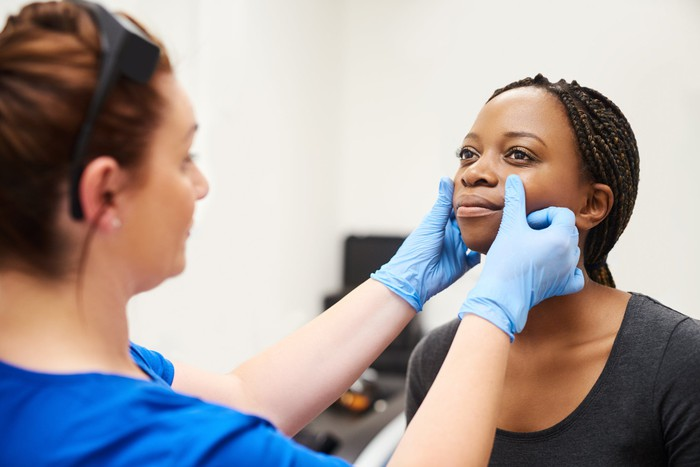 Female patient having her face checked by a medical professional.