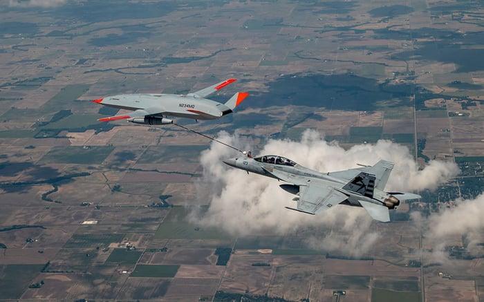 MQ-25 T1 prototype refueling F-18 fighter jet in flight.