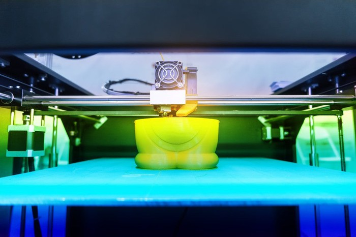 Close-up of a 3D printer producing a bright yellow plastic object.