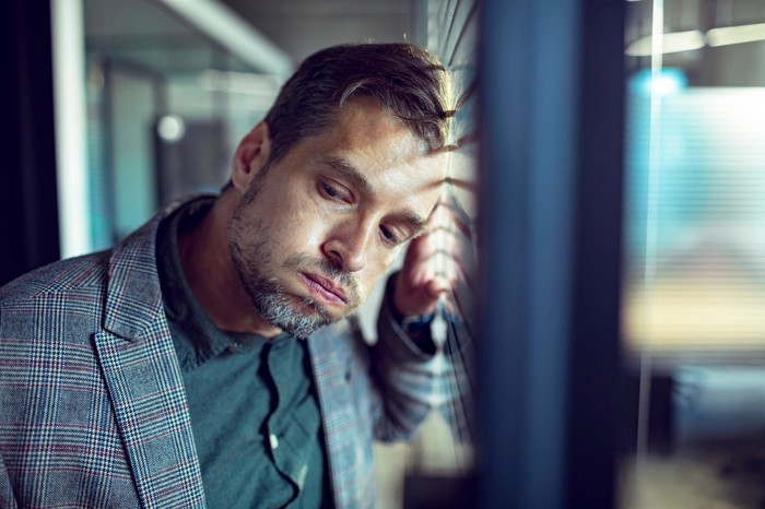 A man disappointed leaning against a window.