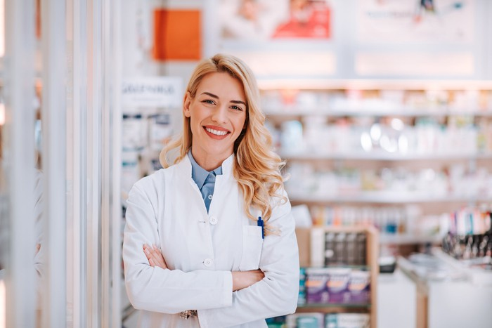 Pharmacist leaning against a wall inside a pharmacy.