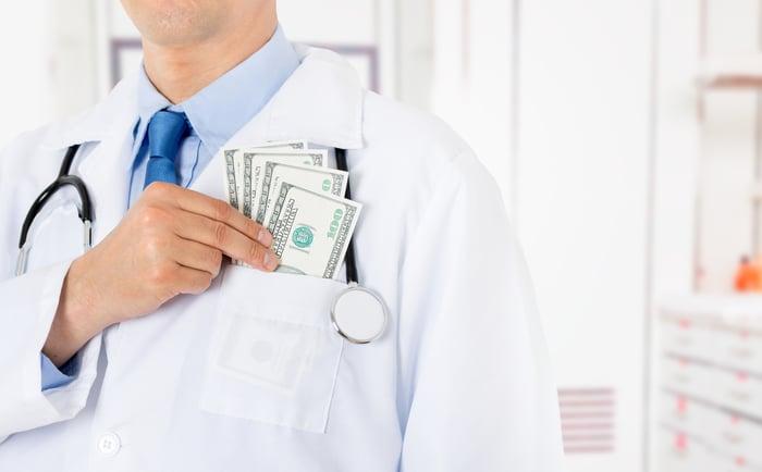 A doctor putting dollar bills inside their front pocket.