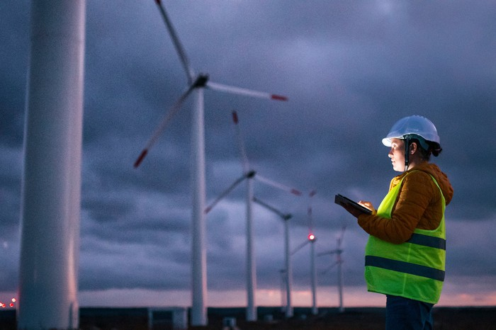 A person holding a tablet looking at wind turbines.