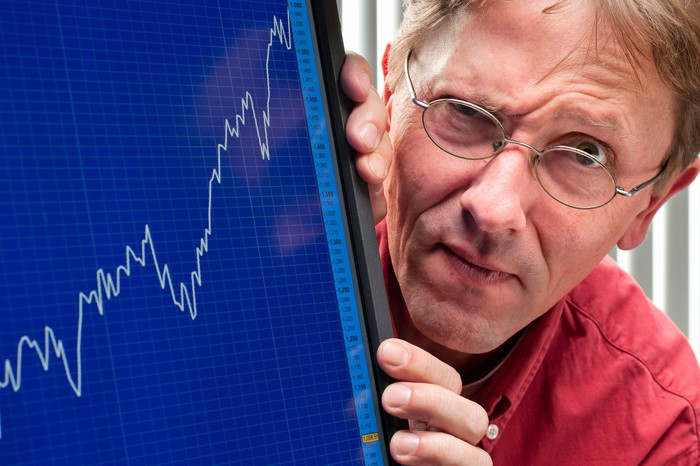 Close-up of a person with a raised eyebrow and a computer monitor showing a positive stock exchange chart.