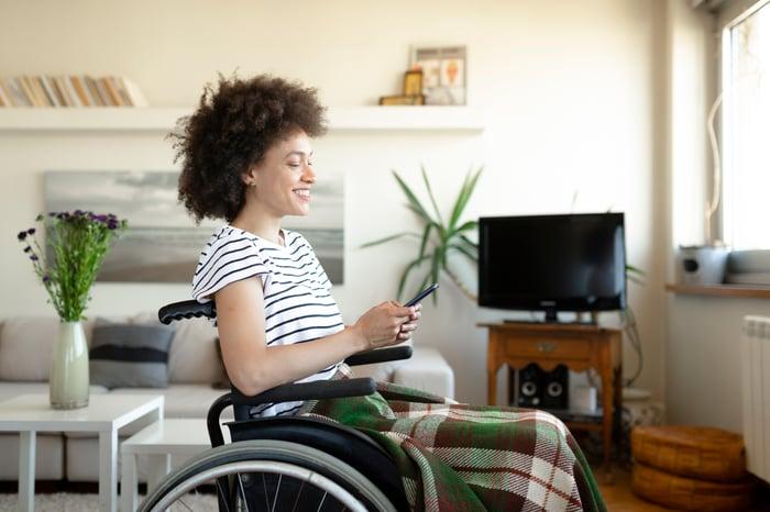 Adulte en fauteuil roulant, souriant en regardant son smartphone.
