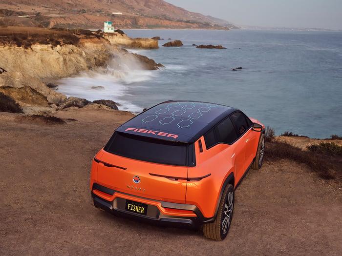 Orange SUV électrique Fisker Ocean garé sur une falaise face à l'océan.