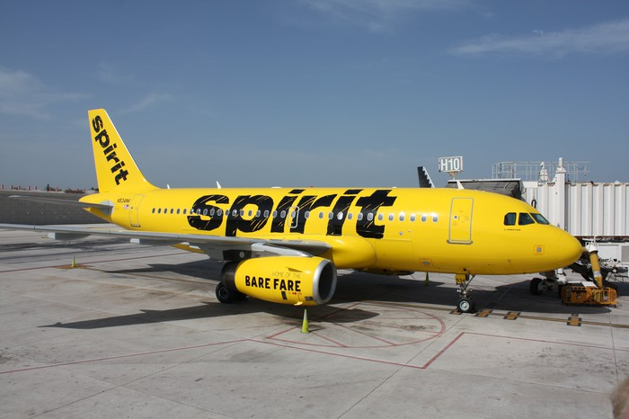 A Spirit Airlines jet parked at an airport gate.