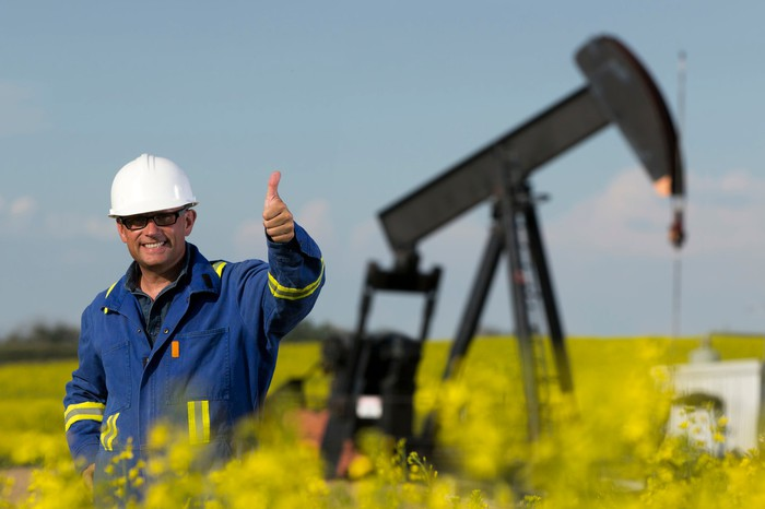 Worker giving thumbs up in front of oil well