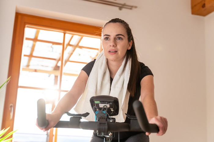 A young woman using an exercise bike at home in front of an open window.