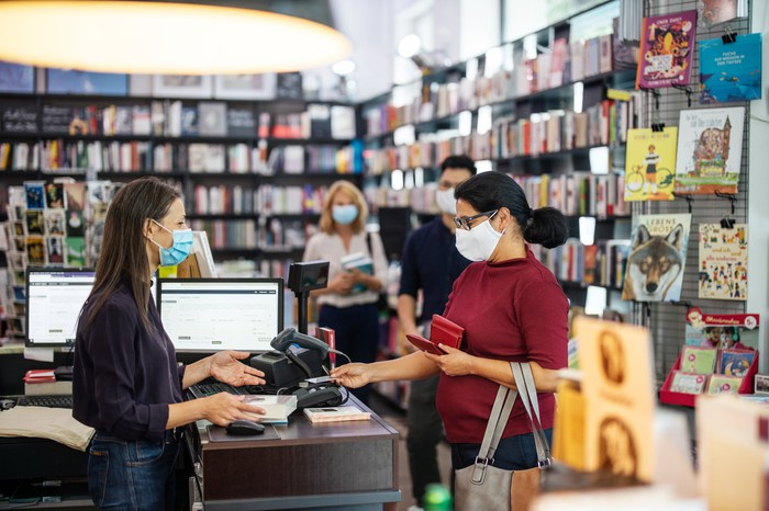 A customer making a purchase in a bookstore where everyone is wearing a COVID mask.