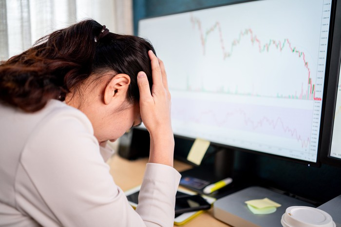 A woman holds her head in her hands while in front of a computer screen with a falling stock chart.