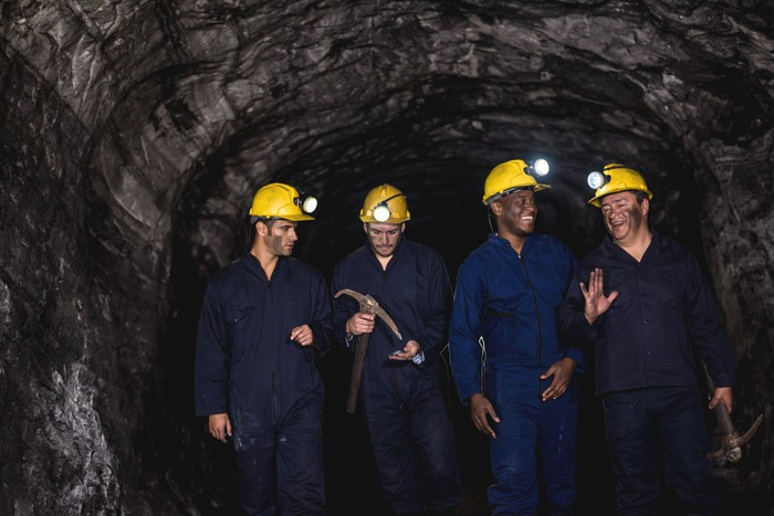 A group of people in protective gear in a mine.