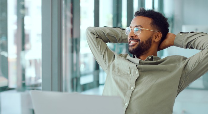 Smiling person at laptop looking out window