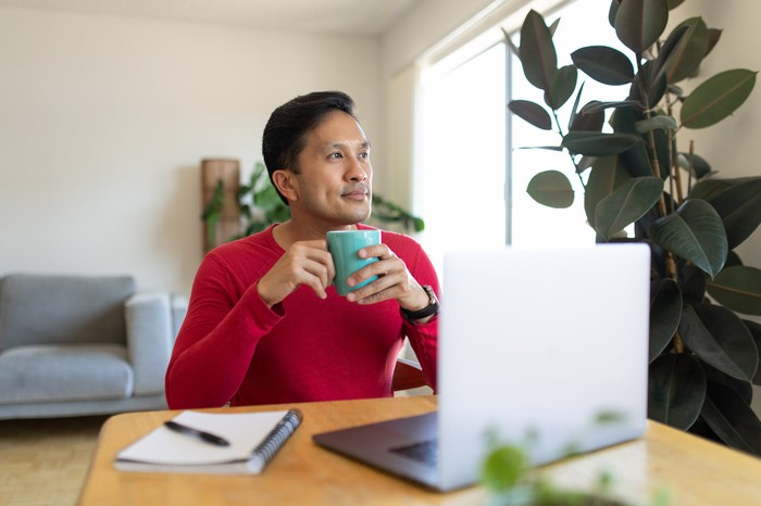 Person at laptop holding mug