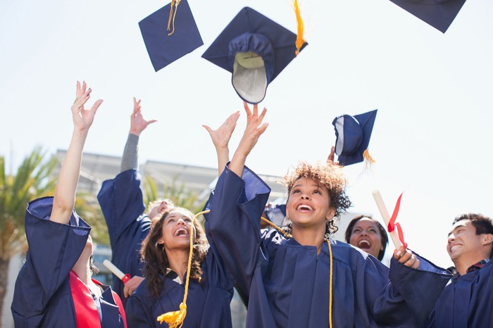 Group of graduates toss their caps in the air.