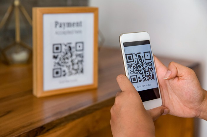 A person makes a payment by scanning a QR code with a phone.