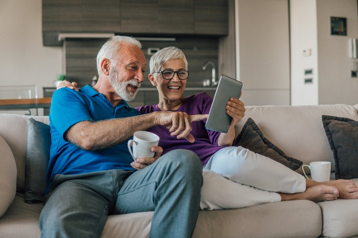 Two people using a tablet computer together on the sofa.