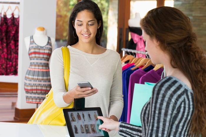 Un client et un vendeur interagissent avec des appareils dans un magasin de vêtements.