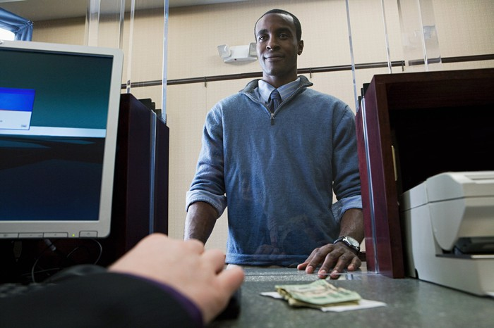 Person at bank with money on counter from viewpoint of teller.