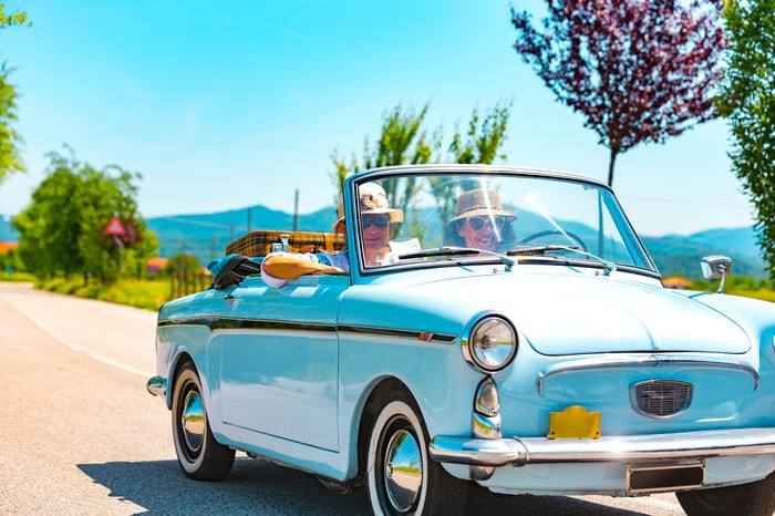 Two people driving down the road in a vintage car.