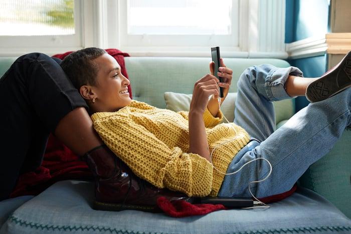 Un jeune se prélasse sur les jambes d'une autre personne sur un canapé bleu tout en faisant défiler son téléphone.