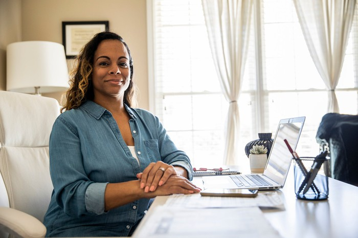 Smiling person sitting at a desk at home in front of a laptop.
