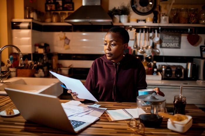 Personne assise devant un ordinateur portable et tenant une feuille de papier.