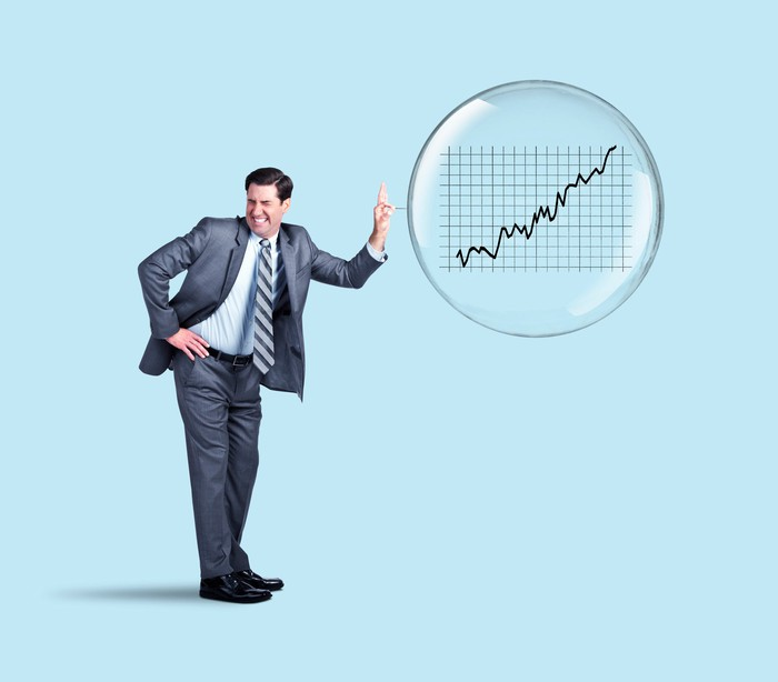 Man in suit poking a stock market bubble with a pin.