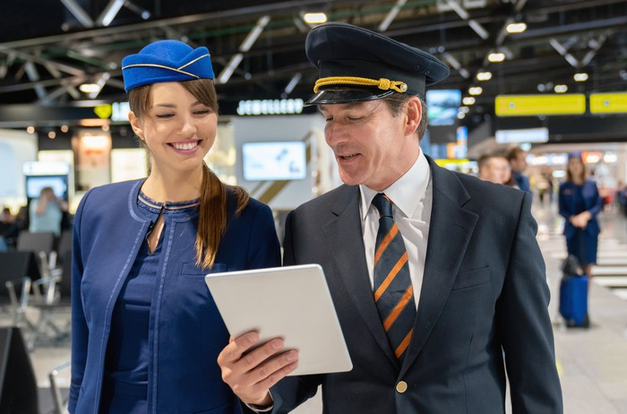 Pilot and flight attendant looking at a tablet.