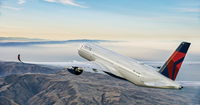 A Delta Air Lines Airbus A350 flying over mountainous terrain.