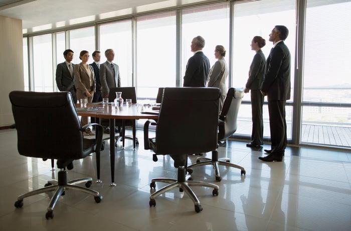 Des dirigeants d'entreprise divisés en deux groupes distincts, se faisant face à travers une table de conférence.