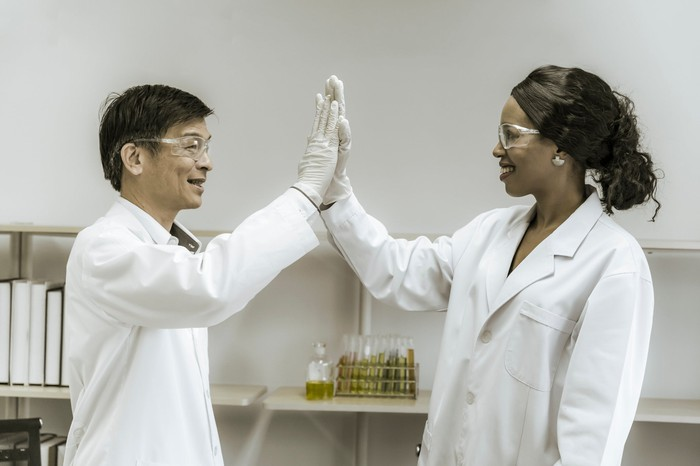 Two medical lab technicians high-fiving each other