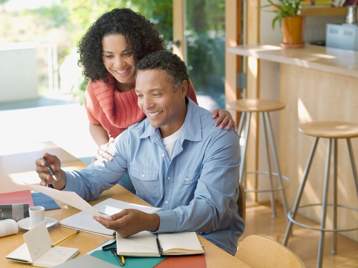 Smiling couple reviews paperwork at table at home.