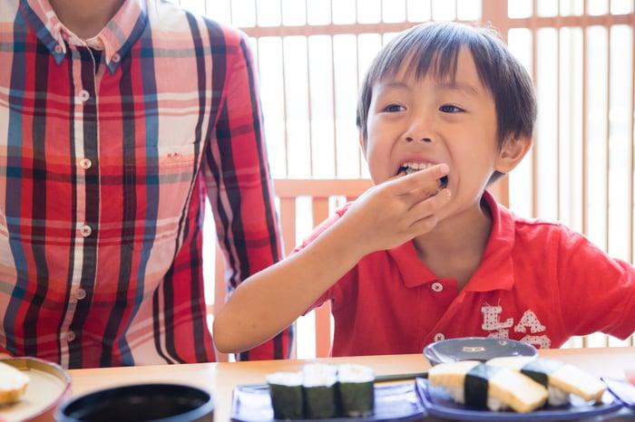 Young boy enjoying a sushi meal.