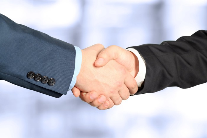 Two people are shaking hands.