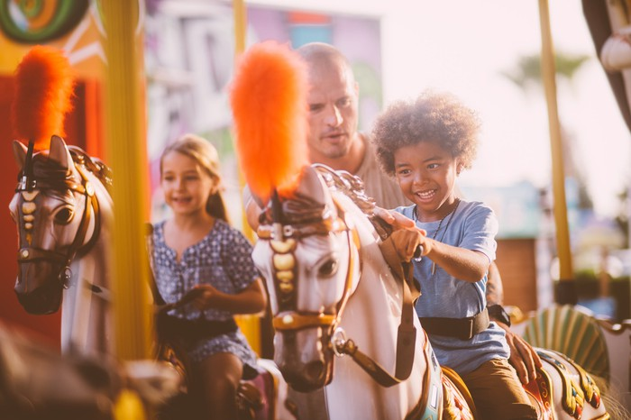 An adult standing between two children riding horses on a merry-go-round.