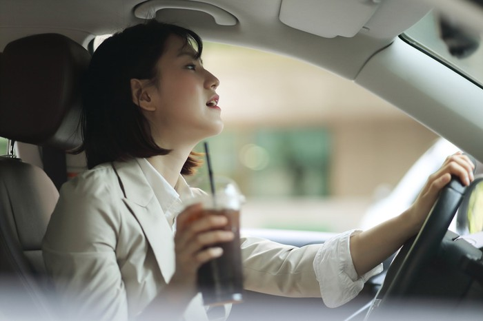 A woman in a car with a  beverage in hand.
