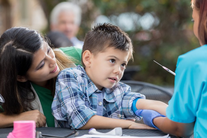 A healthcare worker prepares to draw blood from a child being supported by an adult.