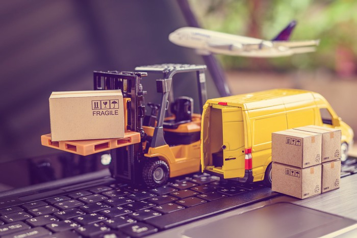 A small forklift, delivery van, and airplane placed on an open laptop.