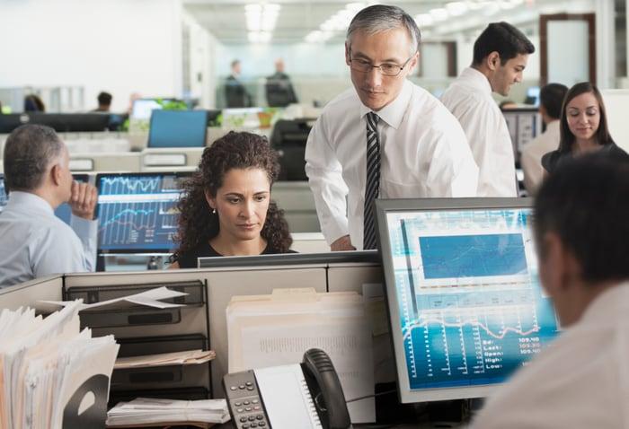 Un bureau ouvert avec des gens devant leurs ordinateurs qui consultent des données financières sur des écrans.