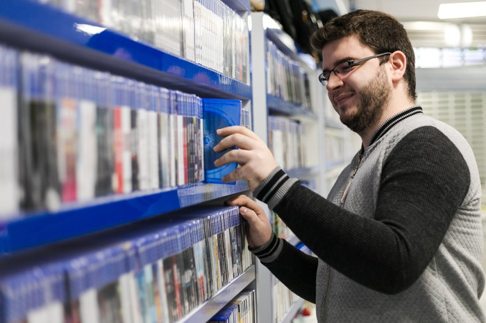 A customer pulling a packaged game off a shelf at a retail store.