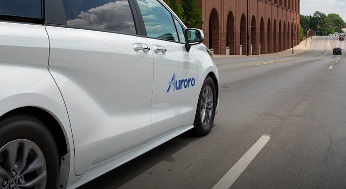 A white Toyota minivan with self-driving sensors and an Aurora logo on its door.