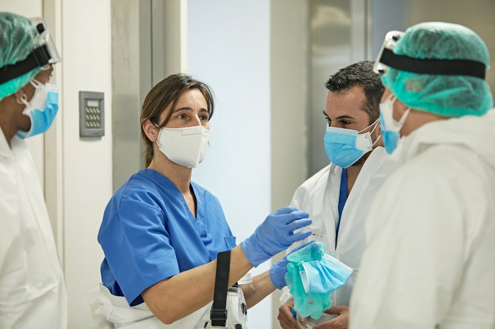 Four doctors talk while wearing personal protective gear in a hospital.