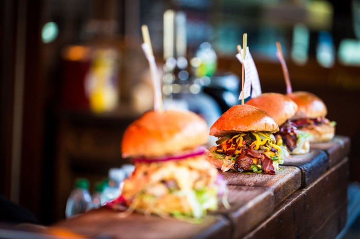Four burgers heaped with toppings lined up on a restaurant counter.
