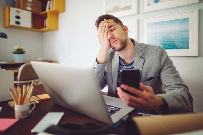Un investisseur tient sa paume contre son visage avec regret alors qu'il exprime sa consternation et regarde son téléphone et son ordinateur portable.