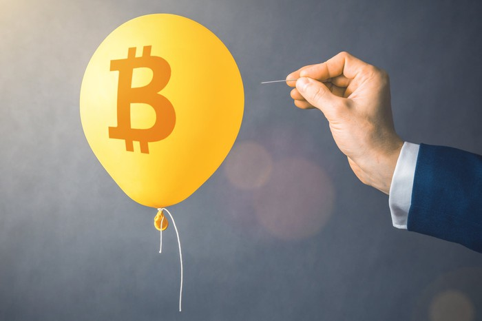 A hand holds a needle in position to pop a golden balloon bearing the Bitcoin symbol.