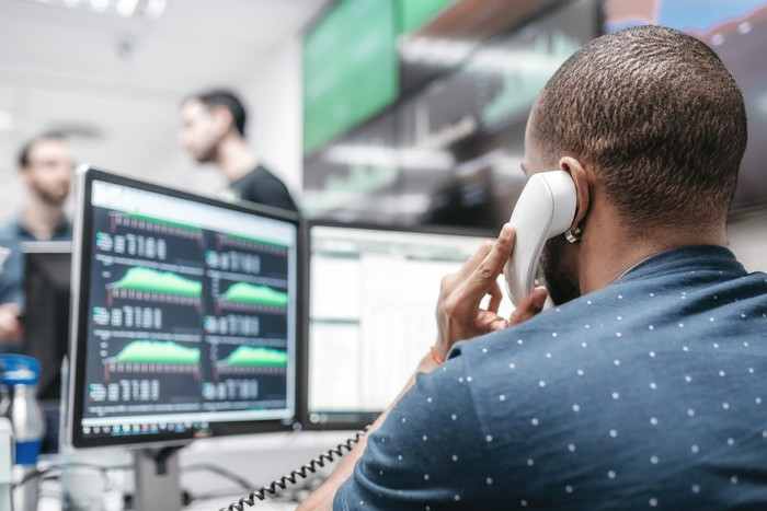 A bond trader is on the phone with economic data on the computer in front of him.
