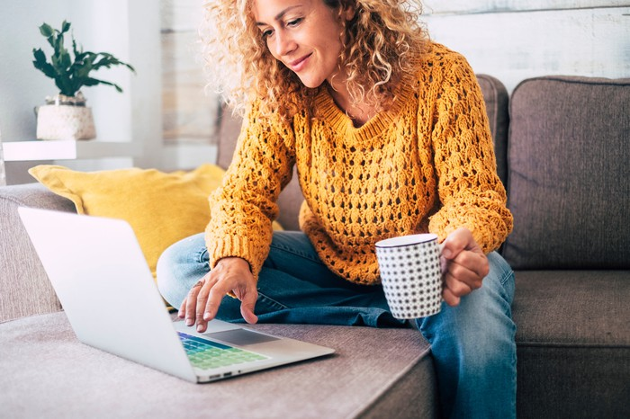 Adult smiling while holding a cup of coffee and looking at her laptop at home.