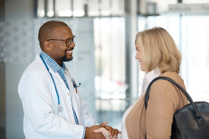 Doctor and patient shaking hands looking happpy.